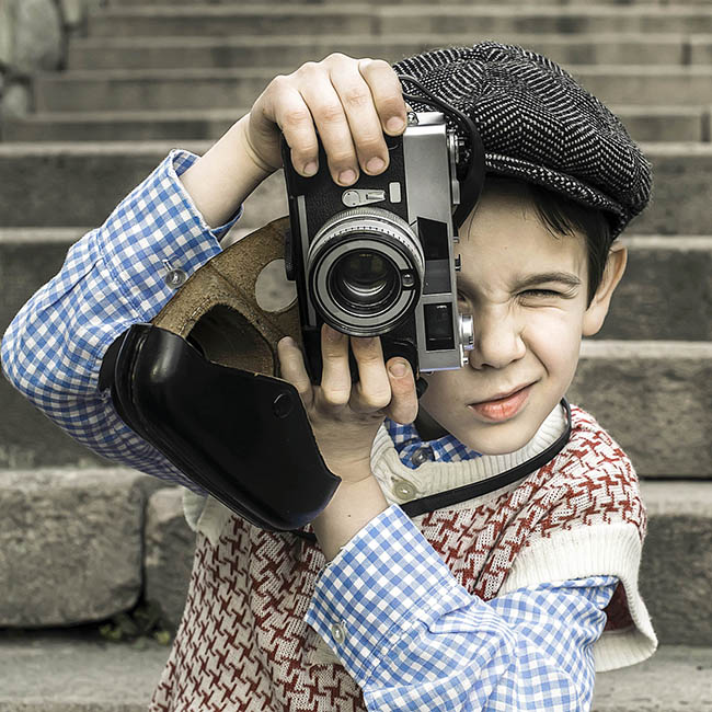 boy using an old vintage camera outside a building
